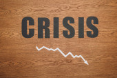 top view of black paper cut word crisis and recession arrow on wooden desk