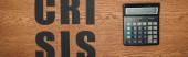 Draufsicht auf schwarzes Papier geschnittenes Wort Krise in der Nähe Taschenrechner auf Holztisch, Panoramaaufnahme