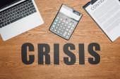 Schwarzwortkrise in der Nähe von Laptop, Taschenrechner und Klemmbrett mit Vertrag auf Holzschreibtisch