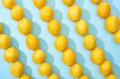 pattern of ripe yellow lemons on blue background with shadows