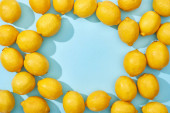 horní pohled na zralé žluté citrony na modrém pozadí se stíny a kopírovat prostor