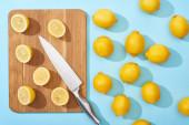 vrchní pohled na zralé žluté řezané citrony na dřevěné řezací desce s nožem na modrém pozadí v blízkosti celé citrony
