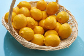 zralé žluté citrony v proutěném koši na modrém pozadí