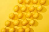 pohled na zralé citrony na žlutém pozadí