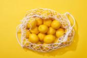 felső nézet friss érett teljes citrom öko húr táska sárga háttér