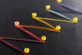 selektivní zaměření mnohobarevných abstraktních propojených čar s kolíky na černém pozadí, koncept připojení a komunikace