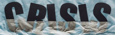 panoramic shot of black word crisis sinking in paper symbolizing water on grey paper background