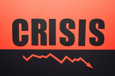 top view of word crisis and recession arrow on black and red background divided horizontally