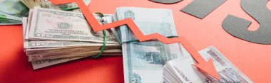 panoramic shot of recession arrow on euro, dollar and ruble banknotes on red background with lighting