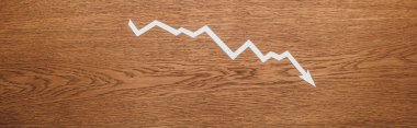 Top view of white paper cut recession arrow on wooden desk, panoramic shot stock vector