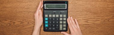 cropped view of female hands near calculator with one hundred thousand on display on wooden desk, panoramic shot