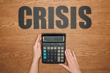 cropped view of female hands near calculator with one hundred thousand on display, and word crisis on wooden desk