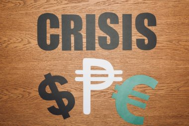 Top view of dollar, peso and euro paper cut symbols, and word crisis on wooden desk stock vector