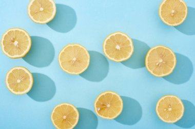 Top view of ripe cut yellow lemons on blue background stock vector