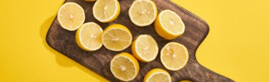 Top view of ripe cut lemons on wooden cutting board on yellow background, panoramic shot stock vector