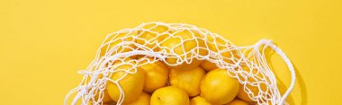 Top view of fresh ripe whole lemons in eco string bag on yellow background, panoramic shot stock vector