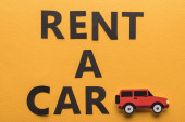 top view of paper cut vehicle and black rent a car lettering on orange background
