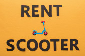 top view of paper cut rent scooter lettering on orange background