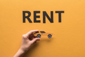 cropped view of woman holding paper cut sports car near rent lettering on orange background