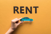 cropped view of woman holding paper cut car near rent lettering on orange background