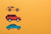 horní pohled na papír řezané auta na oranžovém pozadí s kopírovacím prostorem
