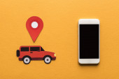 top view of paper cut cars, location mark near smartphone with blank screen on orange background