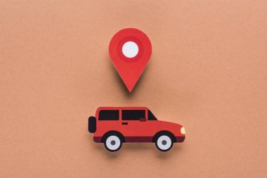 Top view of paper cut car and location mark on brown background, car rent concept stock vector
