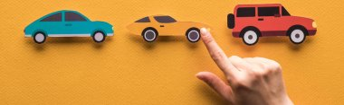 Cropped view of woman pointing with finger at paper cut cars on orange background, panoramic shot stock vector