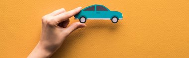 Cropped view of woman holding paper cut car on orange background, panoramic shot stock vector