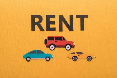 top view of paper cut cars and black rent lettering on orange background