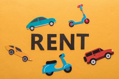 top view of paper cut vehicles and black rent lettering on orange background