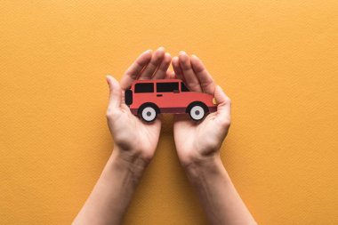 partial view of woman holding paper cut car on orange background