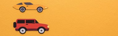 top view of paper cut cars on orange background with copy space, panoramic shot