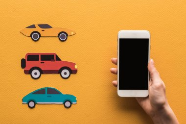 cropped view of woman holding smartphone with blank screen near paper cut cars, location mark on orange background