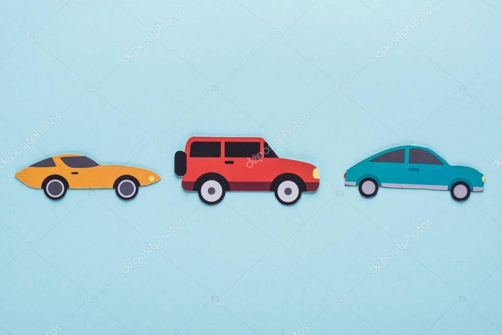 vista dall'alto di carta tagliata varie auto su sfondo blu