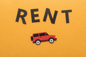 top view of paper cut car and black rent lettering on orange background with copy space