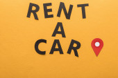 top view of paper cut rent a car lettering with location mark on orange background