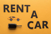 top view of paper cut rent car lettering and key on orange background