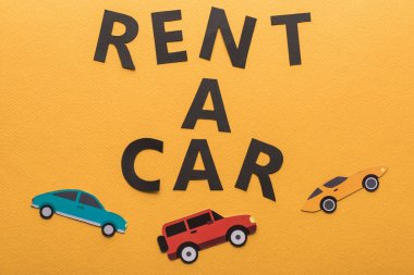 top view of paper cut vehicles and black rent a car lettering on orange background