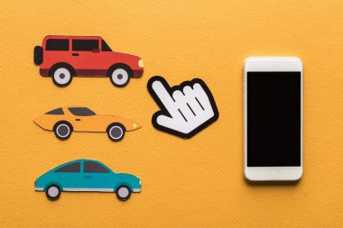 top view of paper cut cars, pointing hand and smartphone on orange background