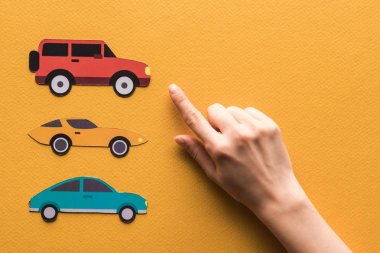 Cropped view of woman pointing with finger at paper cars on orange background stock vector