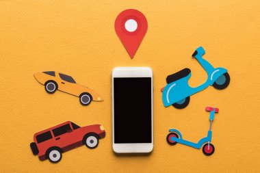 top view of paper cut vehicles near location mark and smartphone with blank screen on orange background