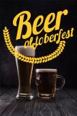 Glas und Becher frisches helles Bier mit Schaum auf Holztisch mit gelbem Oktoberfest-Schriftzug