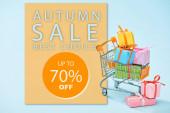 festlich verpackte Geschenke im Warenkorb auf blauem Hintergrund mit Herbstverkauf, bis zu 70 Prozent Rabatt auf Abbildung