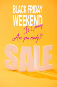 white sale lettering on bright orange background with black Friday weekend illustration