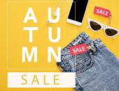 vrchní pohled na džíny, brýle a smartphone se sluchátky s prodejními etiketami na žlutém pozadí s podzimní prodej ilustrace