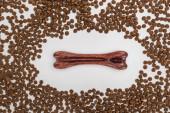vrchní pohled na suché krmivo pro domácí mazlíčky rozptýlené kolem kosti izolované na bílém