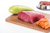 selektivní zaměření suchého krmiva pro domácí zvířata v misce v blízkosti syrového masa, mrkve a cukety na dřevěné řezné desce izolované na bílém