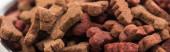 close up view of fresh dry pet food in bones shape, panoramic shot