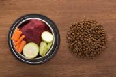 vrchní pohled na suché krmivo pro domácí zvířata v blízkosti syrové zeleniny a masa v misce na dřevěném stole